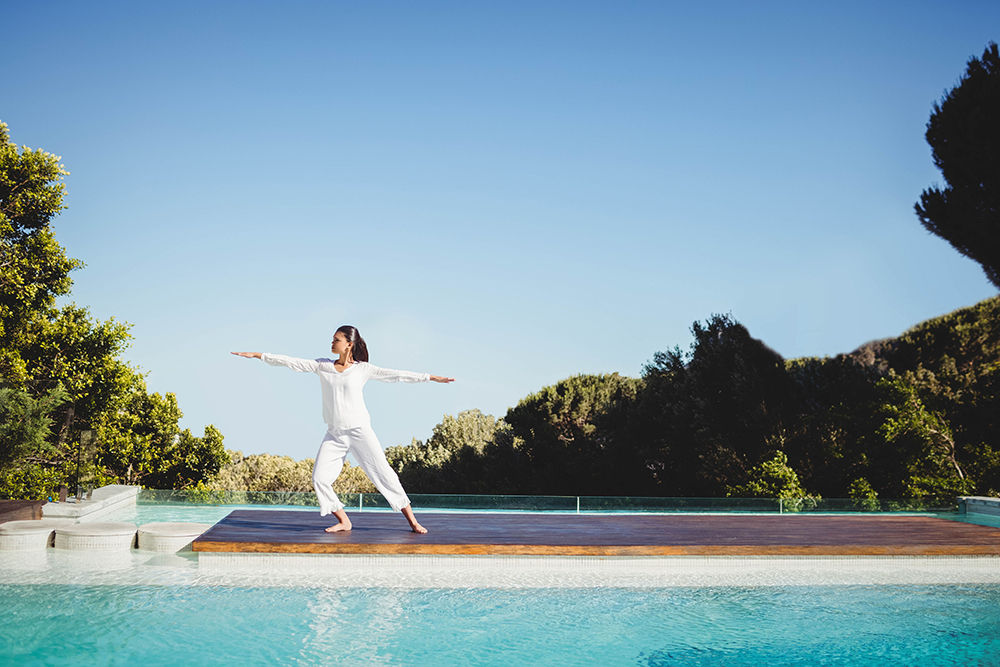 52144402 - calm brunette doing yoga by the pool